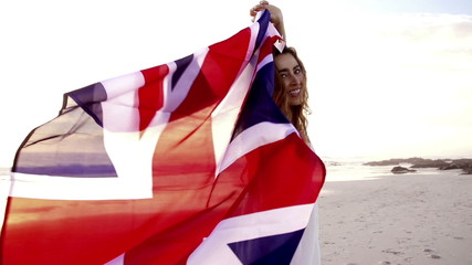 English Woman running with Union Jack on beach