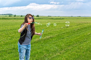 Beautiful Young Woman make Blowing Bubbles
