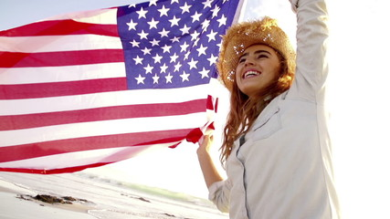 Proud american girl holding stars and stripes in slow motion