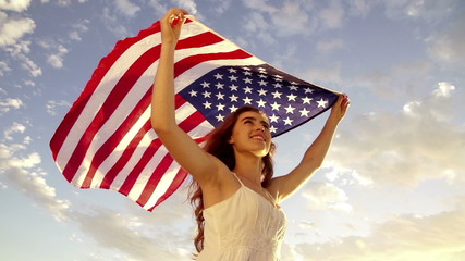 american woman holding stars and stripes against sky