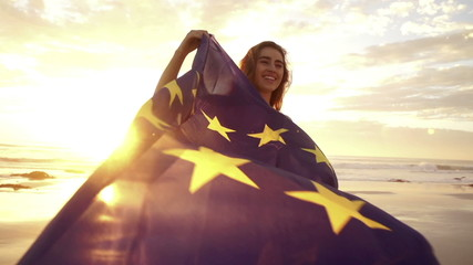 Cheerful woman waving european flag with sun flaring at the beach