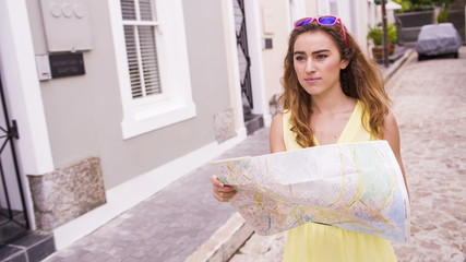 Young tourist using map for orientation during sightseeing