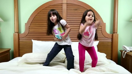 Girls dancing in the bed.