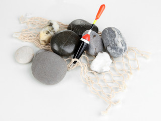 Fishing float with stones isolated on white