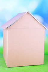 Cardboard house on table on bright background