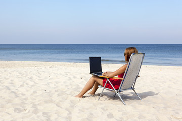 Woman is sitting with laptop on the beach.