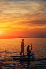 Couple engage standup paddle boarding and meets dawn in ocean