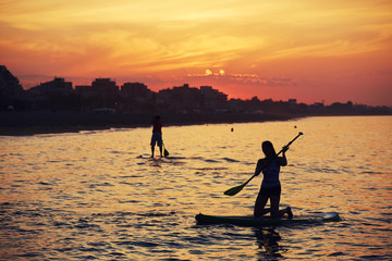 Silhouettes of perfect couple engage standup paddle boarding