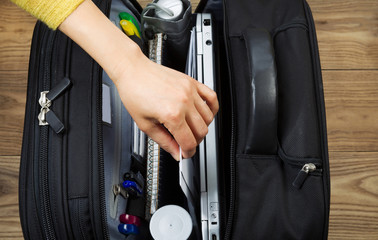 Female Hand taking out office supplies from travel bag