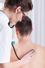 Doctor examines the patient's lungs