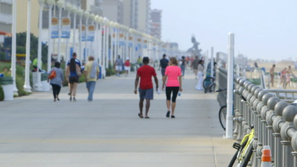 Tourists walk on Virginia Beach boardwalk