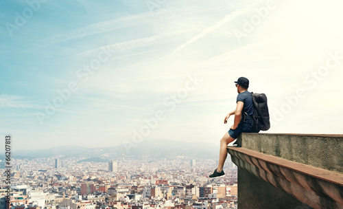 young man sitting on a roof and looking city