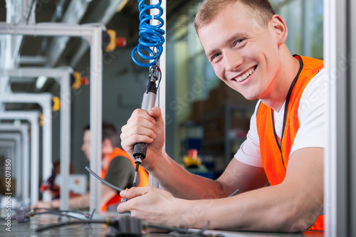 Young smiling man working on the production line - 66207850