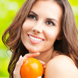 Young woman with persimmon fruit, outdoors