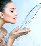 Beautiful smiling model girl under splash of water over blue