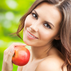 Young woman with red apple, outdoors