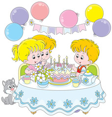 Little girls and boy at the table with a birthday cake