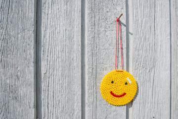 Happy yellow smiley hanging on a wall