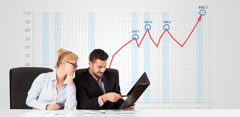Businessman and businesswoman calculating stock market with risi