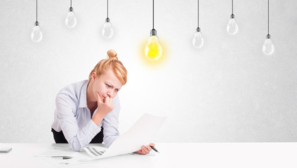 Business woman sitting at table with idea light bulbs