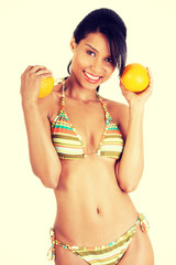 Happy summer woman in bikini with oranges.