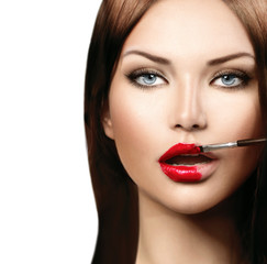 Beauty fashion model girl applying red lipgloss