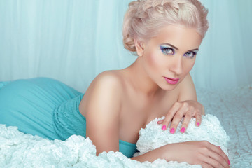 Sensual beautiful blond woman model with eyes makeup posing on b
