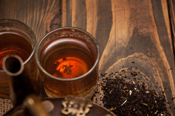 Glass of hot tea and leaves on dark wooden background