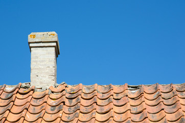 Chimney at an old broken tiled roof