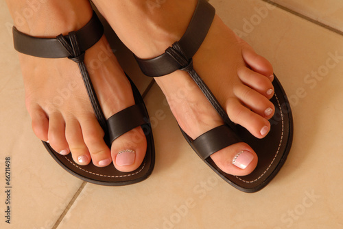 leather sandals on woman's feet - 66211498