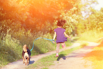 Little girl with dog running in the countryside
