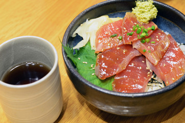 Raw tuna on rice in black bowl