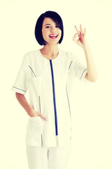 Young female doctor or nurse gesturing perfect