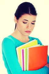 Sad female student with workbook.