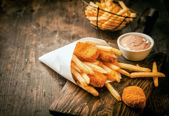 Crumbed fried fish nuggets with potato chips