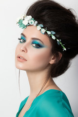 Portrait of young brunette girl in turquoise dress with flower d