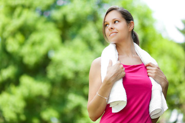 Woman running at the park holding a towel