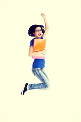 Happy female student jumping with a notebook