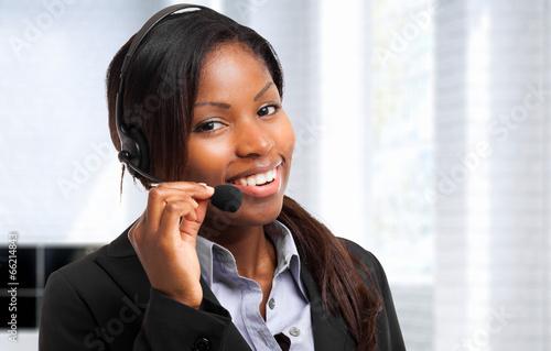 Leinwanddruck Bild Young woman working as an helpdesk