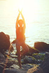 Silhouette hipster girl in yoga pose on the sea background