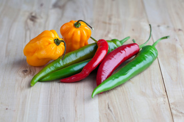 Mix of hottest peppers on wooden table
