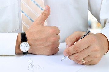 Businessman  signing a document and showing OK sign with his thu