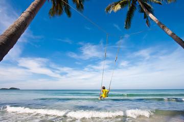 Boy on a swing in sea