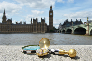 Magnifying glass and compass against British Parliament.