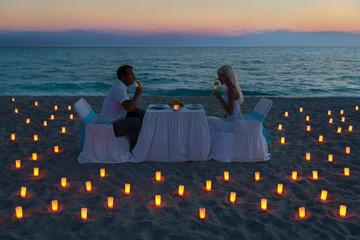 lovers couple share a romantic dinner on sea beach