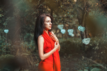 Fabulous girl in a red dress standing in the garden with hearts