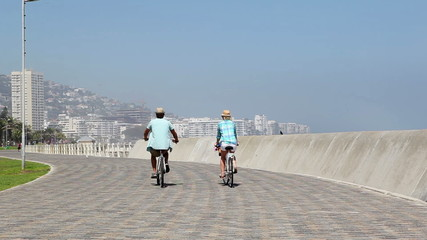 Couple going for a bike ride by the seaside