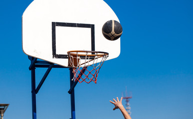 basketball ball falling into basket on blue sky background