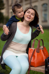 Happy young mother playing with her little son in park