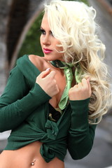Sexy busty blonde young woman posing outdoor in green outfit